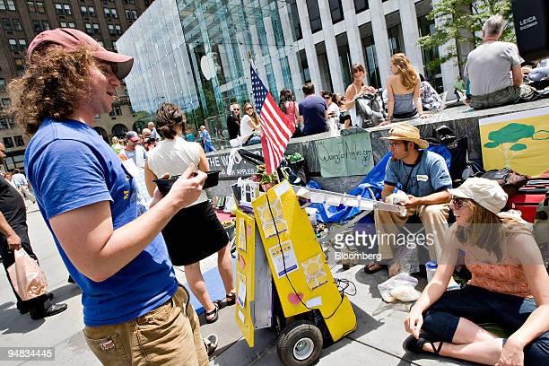 Sam Gensburg left Casey Gustowarow center and Kaitlin Borstelmann wait outside the Apple Store on Fifth Avenue in New York US on Thursday July 10...