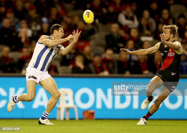 Sam Gibson of the Kangaroos handballs during the round 18 AFL match between the Essendon Bombers and the North Melbourne Kangaroos at Etihad Stadium...