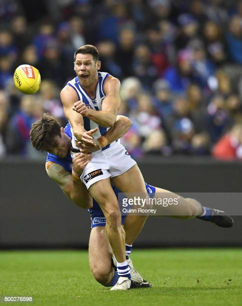 Sam Gibson of the Kangaroos handballs whilst being tackled Tom Campbell of the Bulldogs during the round 14 AFL match between the Western Bulldogs...