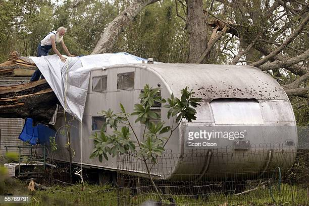 Sam Giegler puts a tarp over a hole in the roof of a friends vintage camper trailer after Hurricane Rita dropped a tree though its roof September 25...