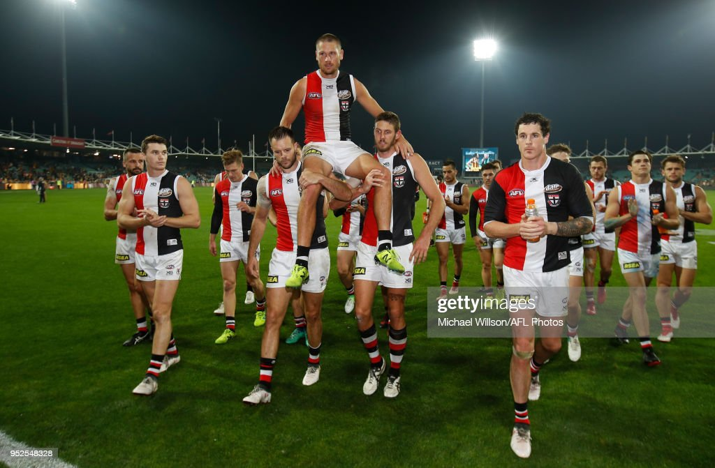 Sam Gilbert of the Saints is chaired from the field after his 200th match by teammates Nathan Brown (left) and Tom Hickey during the 2018 AFL round six match between the Hawthorn Hawks and the St Kilda Saints at UTAS Stadium on April 28, 2018 in Launceston, Australia.