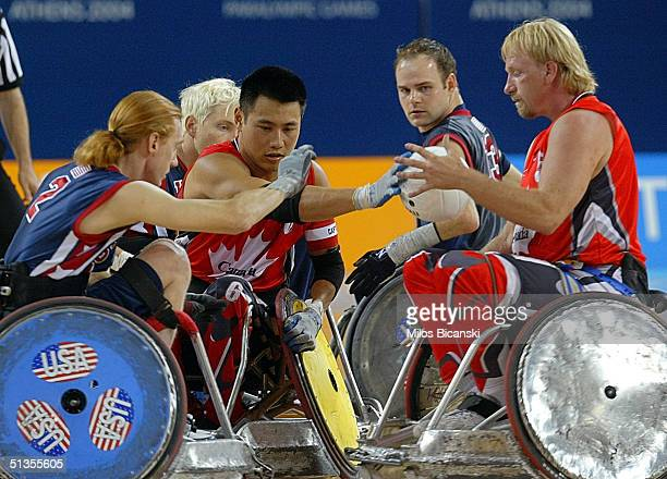 Sam Gloor and Mark Zupan of the US try to regain control of the ball from Garett Hickling and Ian Chan of Canada during the semifinal Wheelchair...