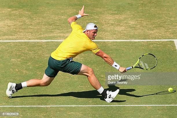 Sam Groth of Australia plays a backhand volley in his match against John Isner of the United States during the Davis Cup tie between Australia and...