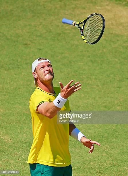 Sam Groth of Australia throws his racquet in the air after losing a game during the reverse singles match between Sam Groth of Australia and Mikhail...