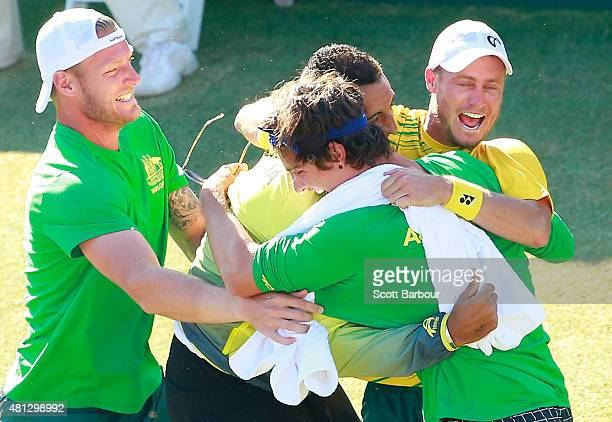 Sam Groth, Thanasi Kokkinakis and Nick Kyrgios run on court to congratulate teammate Lleyton Hewitt of Australia as he celebrates winning the reverse...
