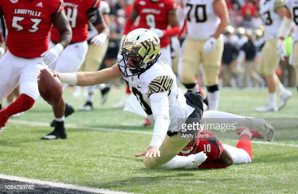 Sam Hartman of the Wake Forest Demon Deacons reaches out to score a touchdown against the Louisville Cardinals on October 27 2018 in Louisville...