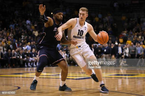 Sam Hauser of the Marquette Golden Eagles dribbles the ball while being guarded by Marvin Clark II of the St John's Red Storm in the first half at...