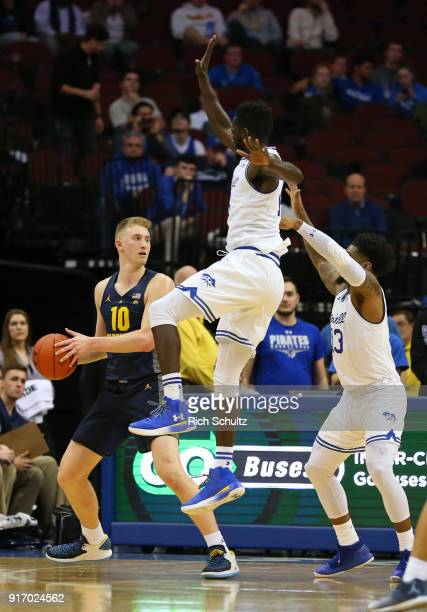Sam Hauser of the Marquette Golden Eagles in action against Ismael Sanogo and Myles Powell of the Seton Hall Pirates in action against the Marquette...