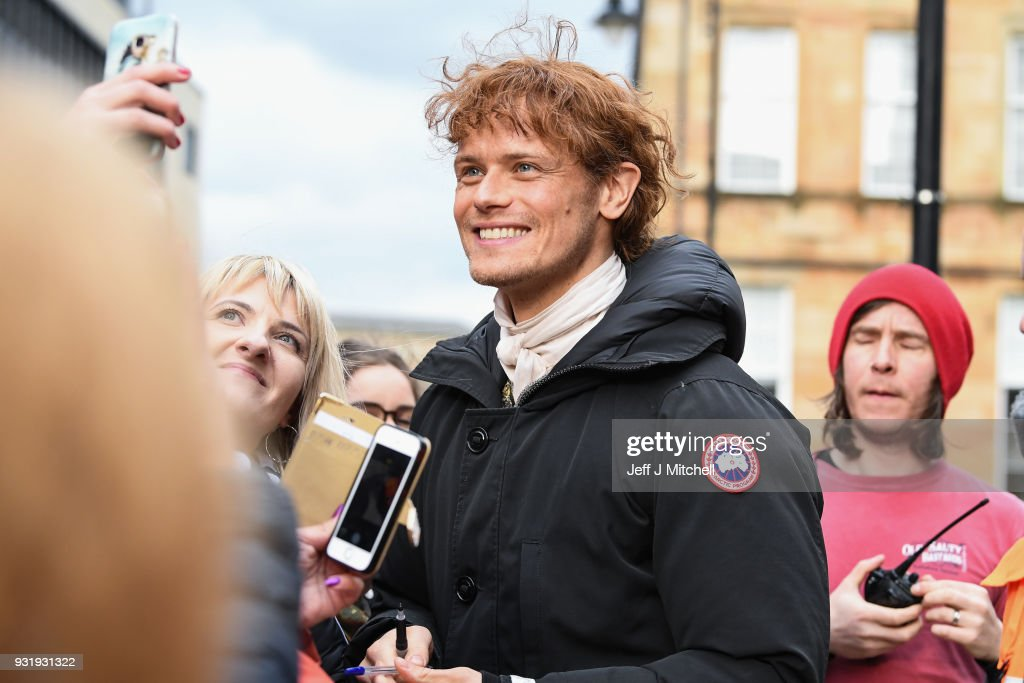 Sam Heughan from the TV series Outlander meets fans who were waiting in St Andrew's Square on March 14, 2018 in Glasgow, Scotland. Dozens of fans have gathered to catch a glimpse of Sam Heughan and co-star Caitriona Balfe as they filmed in the city's Salmarket area for series four of the programme.