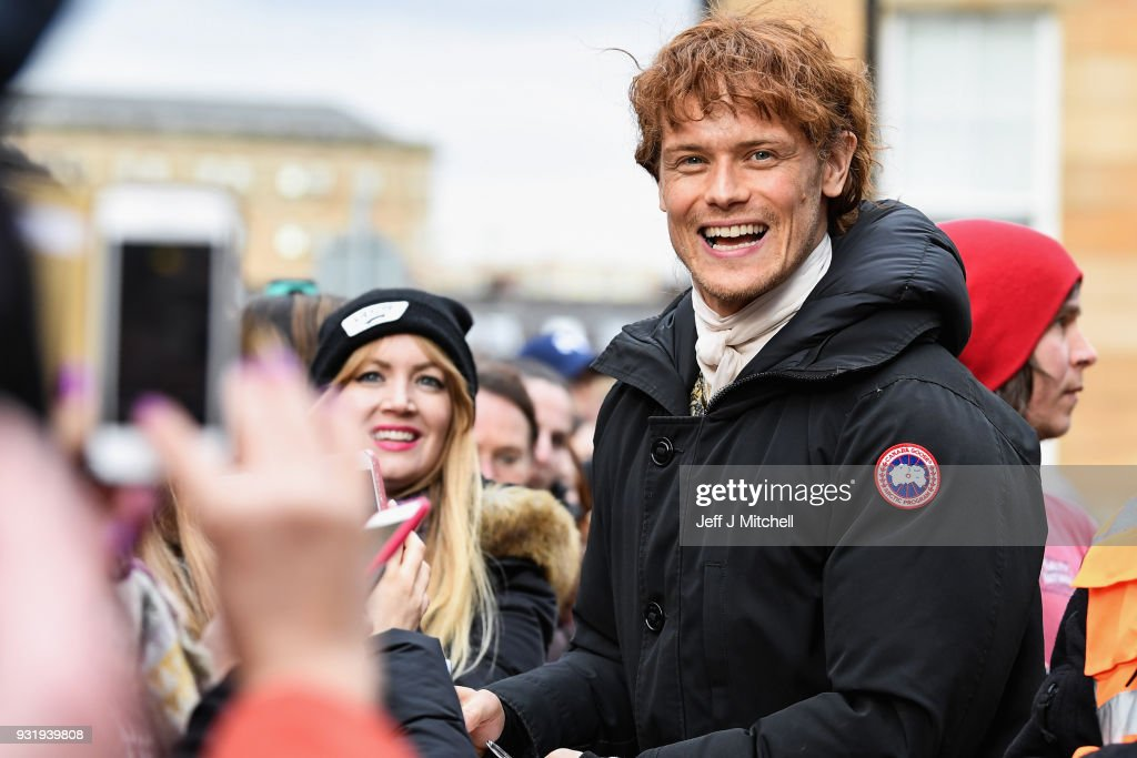 Sam Heughan from the TV series Outlander meets fans who were waiting in St Andrew's Square on March 14, 2018 in Glasgow,Scotland. Dozens of fans have gathered to catch a glimpse of Sam Heughan and co-star Caitriona Balfe as they filmed in the city's Salmarket area for series four of the programme.