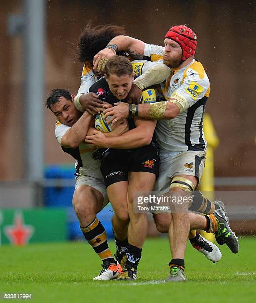 Sam Hill of Exeter Chiefs is tackled by George Smith Ashley Johnson and James Haskell of Wasps during the Aviva Premiership semi final match between...