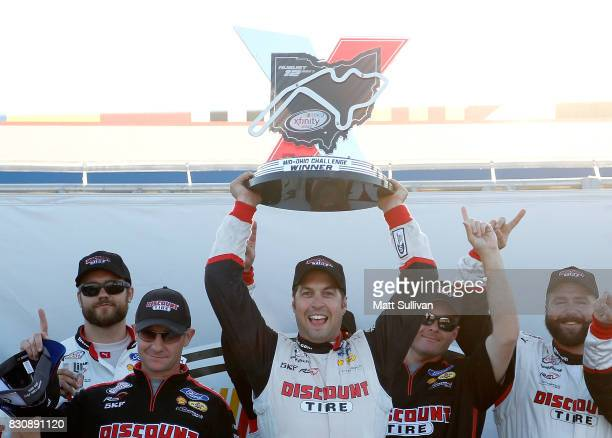 Sam Hornish Jr driver of the Discount Tire Ford celebrates in victory lane with the trophy after winning the NASCAR XFINITY Series MidOhio Challenge...