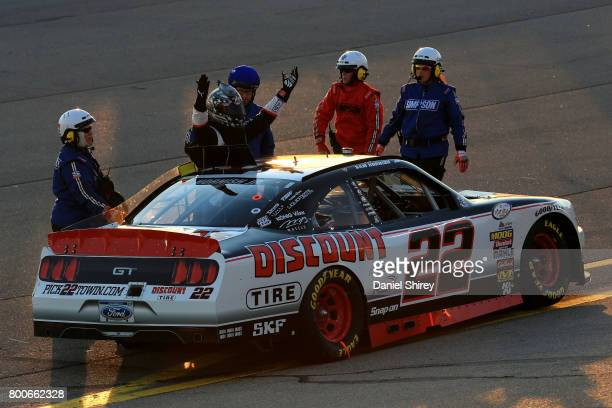 Sam Hornish Jr driver of the Discount Tire Ford reacts towards other drivers while climbing out of his car after an incident during the NASCAR...