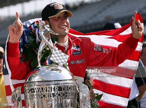 Sam Hornish Jr driver of the Marlboro Team Penske Dallara Honda celebrates with the Borg Warner Trophy after winning the IRL IndyCar Series 90th...