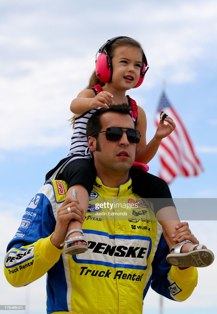 Sam Hornish Jr., driver of the #12 Penske Truck Rental Ford, walks on the grid with his daughter Addison Hornish during qualifying for the NASCAR Nationwide Series U.S. Cellular 250 Presented by Enlist Weed Control System at Iowa Speedway on August 3, 2013 in Newton, Iowa.