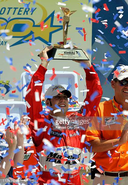 Sam Hornish Jr holds up up the Kansas Lottery Indy 300 trophy after nipping Dan Wheldon at Kansas Speedway in Kansas City Missouri Sunday July 2 2006