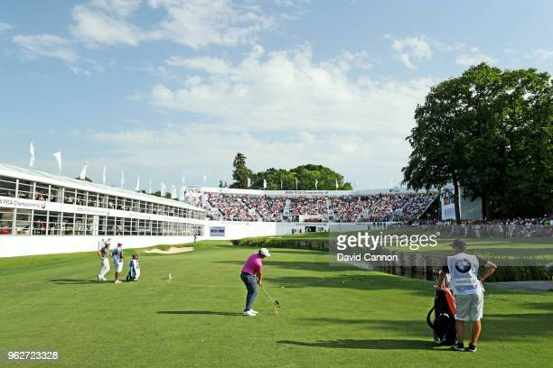 Sam Horsfield of England plays his third shot on the par 5 18th hole as his playing partner Rory McIlroy of Northern Ireland looks on during the...