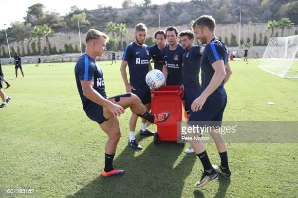 Sam Hoskins of Northampton Town attempts to put the ball into a bin as teammates Sam Foley Ash Taylor JohnJoe O'TooleDavid Buchanan and Dean Bowditch...