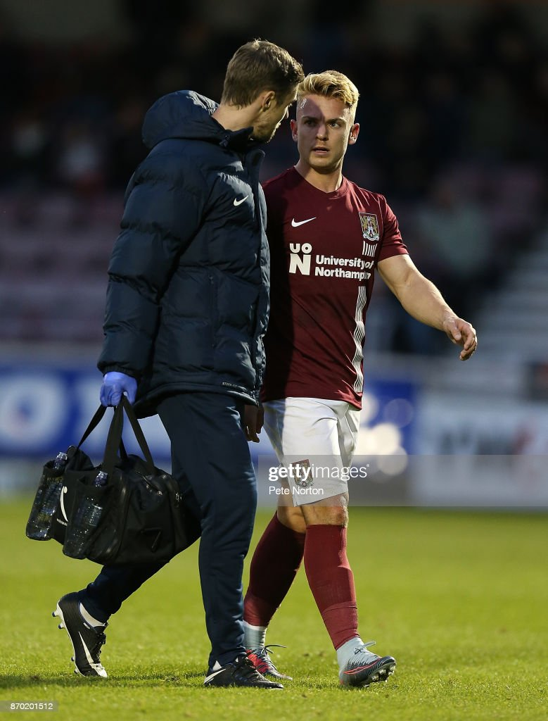 Sam Hoskins of Northampton Town leaves the pitch with physio Anders Braastad during The Emirates FA Cup First Round match between Northampton Town and Scunthorpe United at Sixfields on November 4, 2017 in Northampton, England.