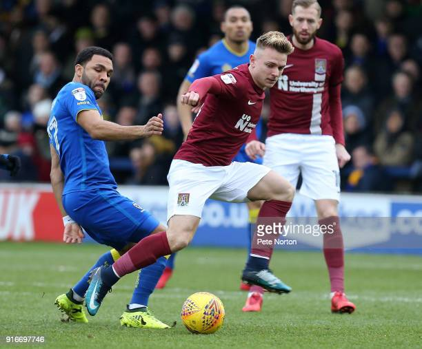 Sam Hoskins of Northampton Town looks to the ball with Andy Barcham of AFC Wimbledon during the Sky Bet League One match between AFC Wimbledon and...