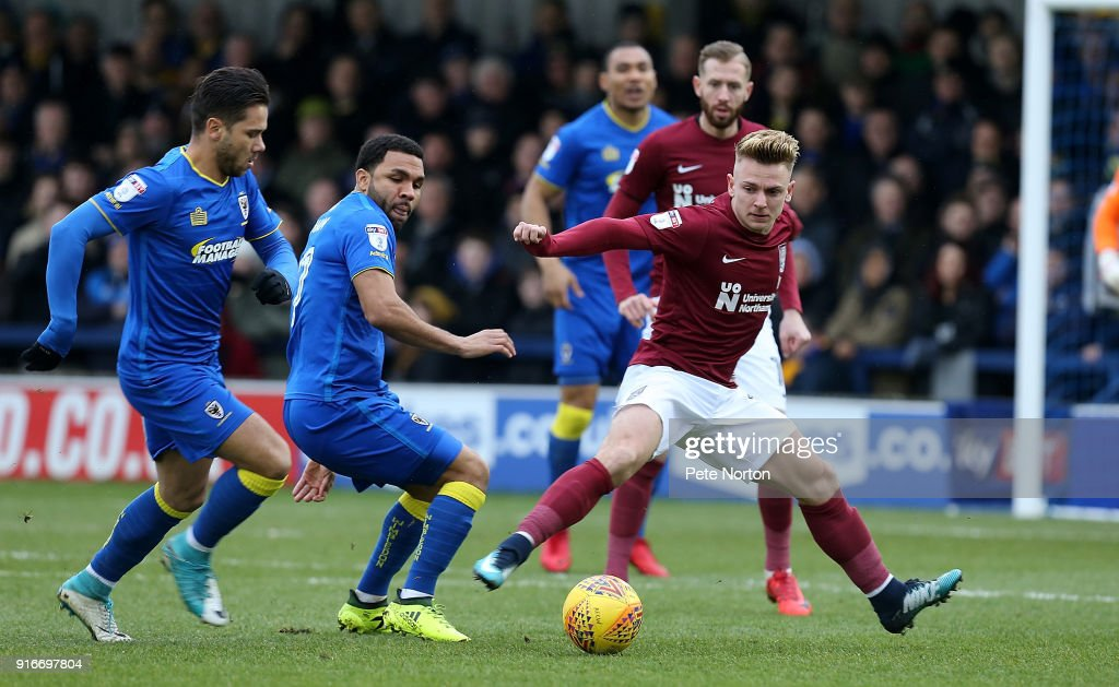 Sam Hoskins of Northampton Town looks to the ball with Harry Forrester and Andy Barcham of AFC Wimbledon during the Sky Bet League One match between A.F.C. Wimbledon and Northampton Town at The Cherry Red Records Stadium on February 10, 2018 in Kingston upon Thames, England.