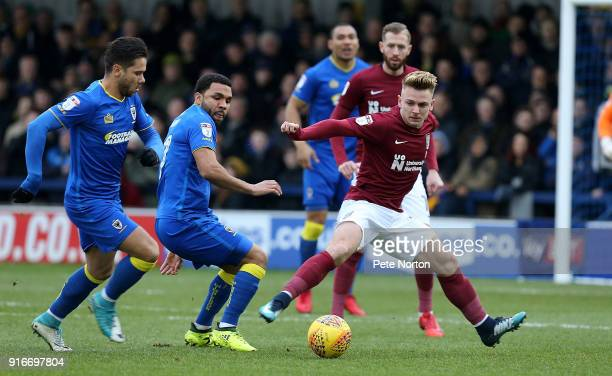 Sam Hoskins of Northampton Town looks to the ball with Harry Forrester and Andy Barcham of AFC Wimbledon during the Sky Bet League One match between...