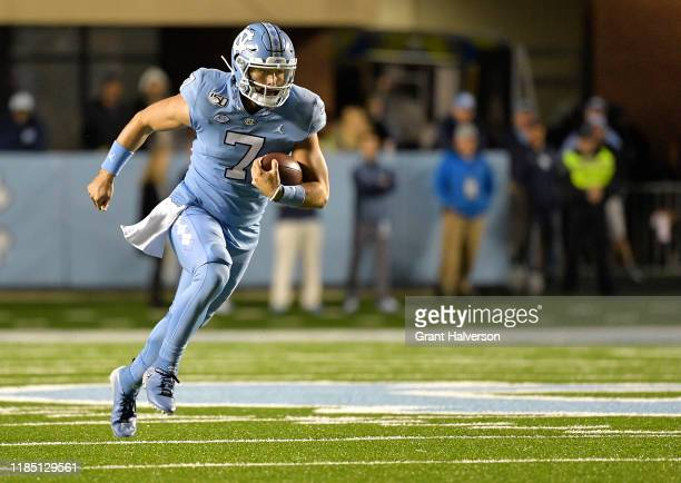 Sam Howell of the North Carolina Tar Heels scrambles against the Virginia Cavaliers during the first half of their game at Kenan Stadium on November...