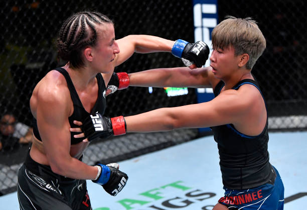 Sam Hughes punches Loma Lookboonmee of Thailand in a strawweight bout during the UFC Fight Night event at UFC APEX on May 01, 2021 in Las Vegas,...