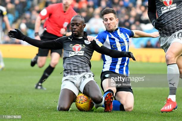 Sam Hutchinson of Sheffield Wednesday and Modou Barrow of Reading compete for the ball during the Sky Bet Championship match between Sheffield...