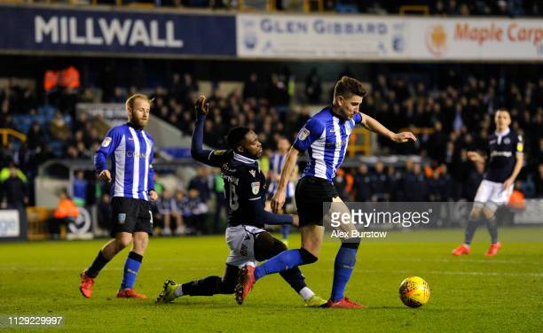 Sam Hutchinson of Sheffield Wednesday tackles Fred Onyedinma of Millwall during the Sky Bet Championship match between Millwall and Sheffield...