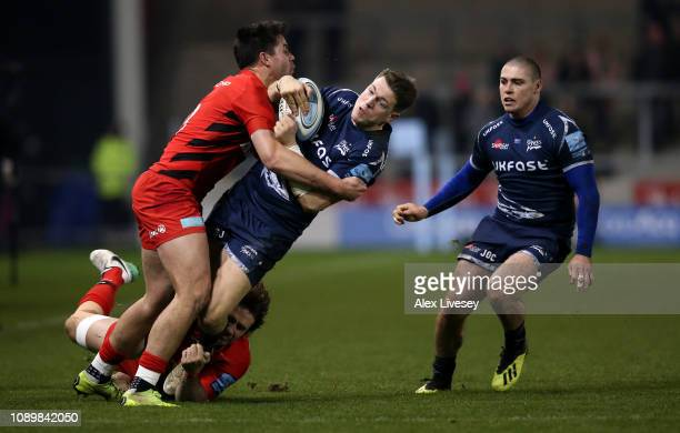 Sam James of Sale Sharks is tackled by Marcelo Bosch and Sean Maitland of Saracens during the Gallagher Premiership Rugby match between Sale Sharks...