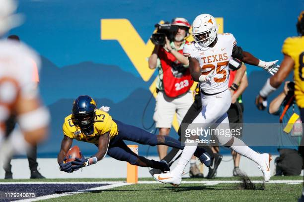 Sam James of the West Virginia Mountaineers dives to make a 44yard touchdown reception behind BJ Foster of the Texas Longhorns in the first quarter...