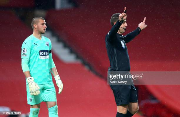 Sam Johnstone of West Bromwich Albion reacts as referee David Coote indicates a VAR review is taking place, to look at a penalty save from Sam...