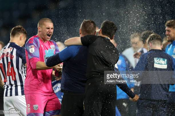Sam Johnstone of West Bromwich Albion sprays champagne as he celebrates promotion to the Premier League on the pitch at the end of the Sky Bet...