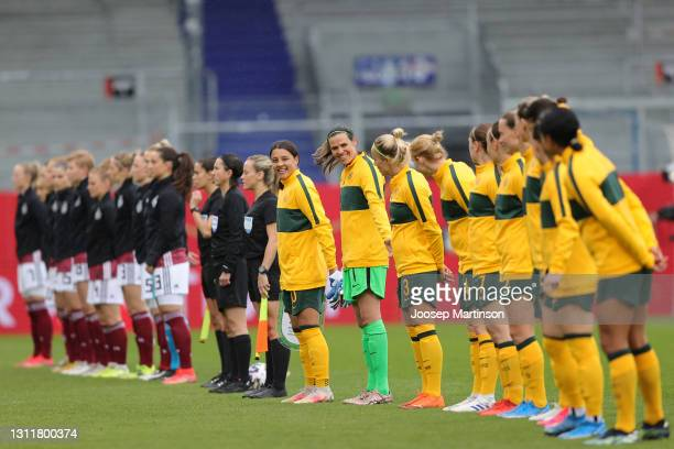 Sam Kerr and Lydia Williams of Australia interact with their teammates as they line up for the national anthem prior to the Women's International...
