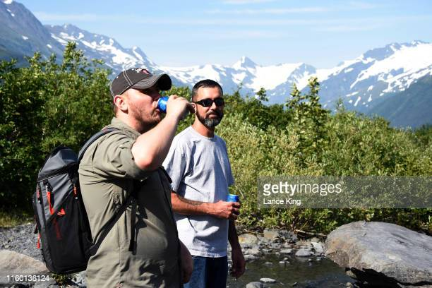 Sam Lightle left from Anchorage and Brandon York from Jacksonville Florida take in the scenery along a creek below the Byron Glacier on July 4 2019...