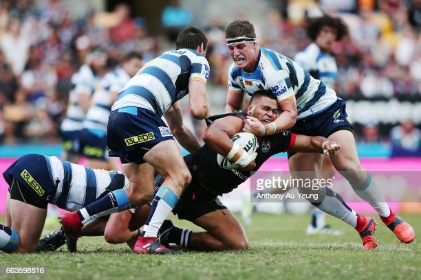 Sam Lisone of the Warriors is tackled by Ryan Simpkins and Jarrod Wallace of the Titans during the round five NRL match between the New Zealand...