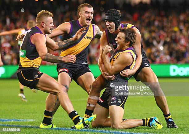 Sam Lloyd of the Tigers is congratulated by Dustin Martin Ben Griffiths and Brandon Ellis of the Tigers after kicking the matchwinning goal after the...