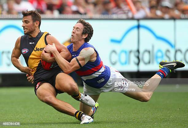 Sam Lloyd of the Tigers is tackled by Robert Murphy of the Bulldogs during the round two AFL match between the Richmond Tigers and the Western...