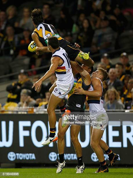 Sam Lloyd of the Tigers takes a spectacular mark over Luke Brown and Rory Laird of the Crows and teammate Shane Edwards of the Tigers during the 2016...