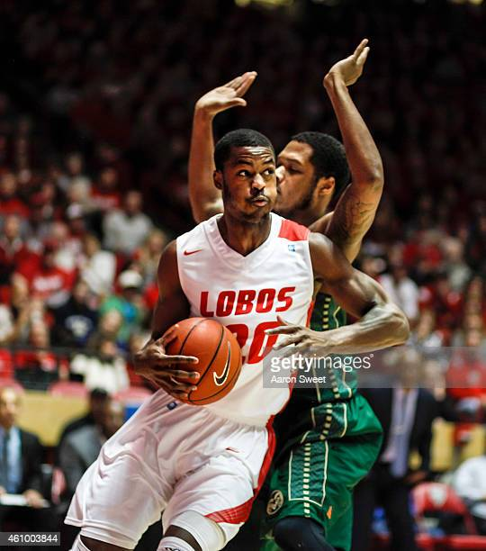 Sam Logwood of the New Mexico Lobos drives to the basket defended by Fred Richardson III of the Colorado State Rams during their game at The WisePies...