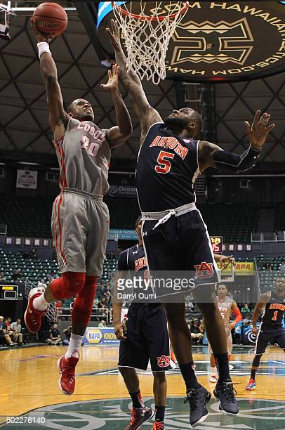 Sam Logwood of the New Mexico Lobos lays the ball in over Cinmeon Bowers of the Auburn Tigers at the Stan Sheriff Center during the Diamond Head...