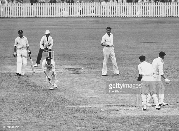 Sam Loxton of Australia stoops to catch MCC captain Freddie Brown off a ball from Jack Iverson on the final day of the First Test at Brisbane Cricket...