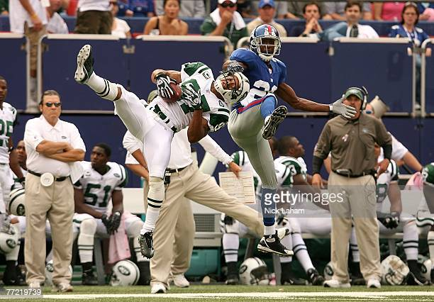 Sam Madison of the New York Giants grabs the mask of Laveranues Coles of the New York Jets after a pass completion at Giants Stadium on October 7...