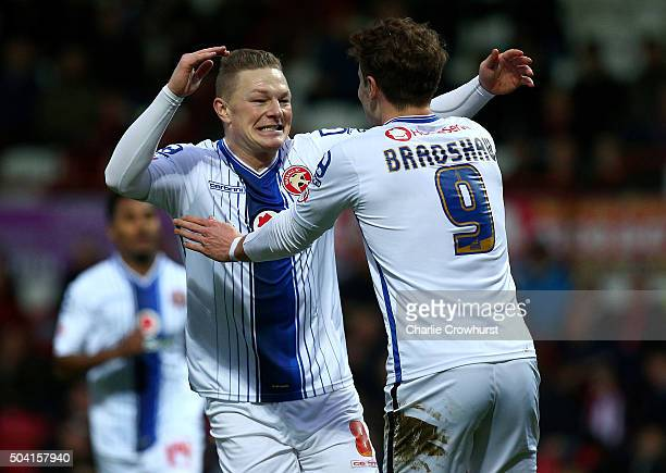 Sam Mantom of Walsall celebrates with team mates after scoring the first goal of the game during the FA Cup Third Round match between Brentford v...