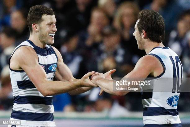 Sam Menegola of the Cats celebrates a goal with Daniel Menzel during the round 23 AFL match between the Geelong Cats and the Greater Western Sydney...