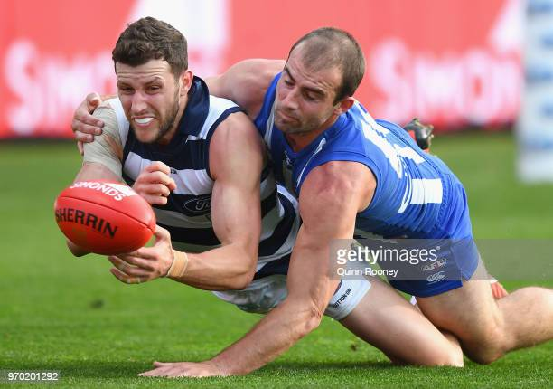 Sam Menegola of the Cats handballs whilst being tackled by Ben Cunnington of the Kangaroos during the round 12 AFL match between the Geelong Cats and...