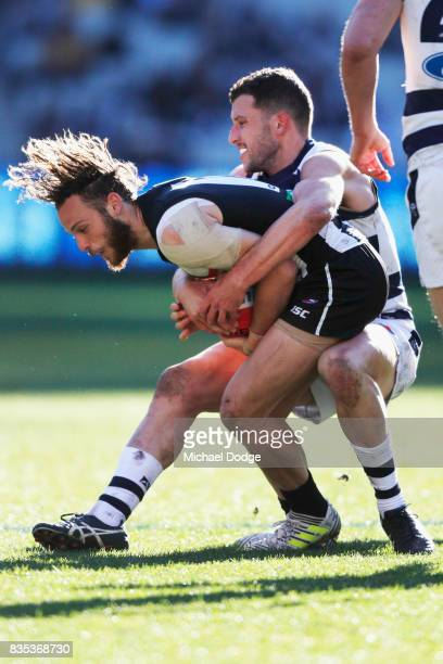 Sam Menegola of the Cats tackles Tim Broomhead of the Magpies during the round 22 AFL match between the Collingwood Magpies and the Geelong Cats at...