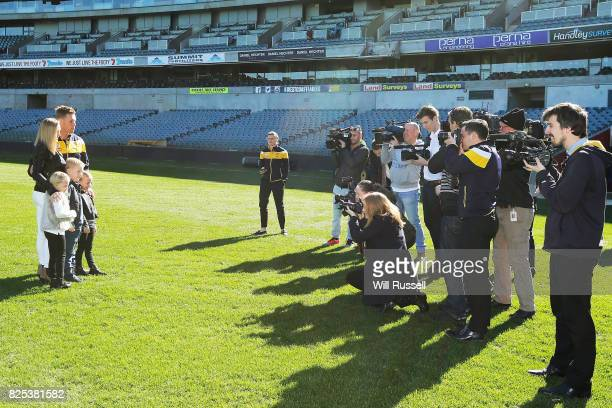 Sam Mitchell and family pose on the oval after speaking to the media announcing his retirement from playing at the end of the home and away season...