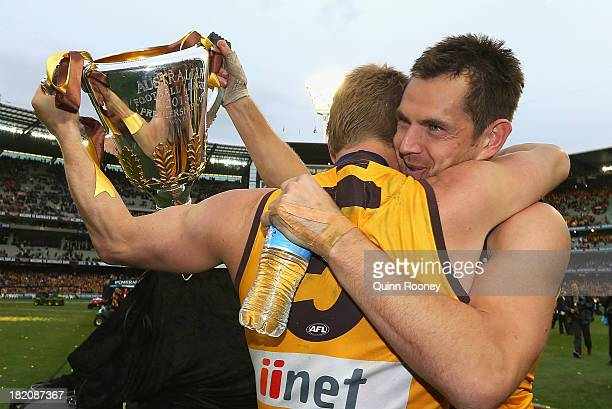 Sam Mitchell and Luke Hodge of the Hawks celebrate with the Premiership Cup after the Hawks won the 2013 AFL Grand Final match between the Hawthorn...